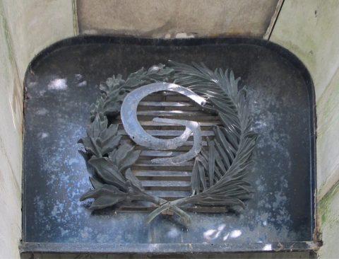 Imposte de la porte de la sépulture Grunwaldt. La lettre « G » est placée entre un rameau de laurier et une palme.