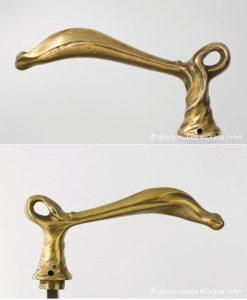 Paire de « poignée de porte en forme de béquille », attribuées à Guimard. Dimensions : larg. 13 cm, haut. 6 cm. Musée d'Orsay. Numéros d'inventaire AOA 1742 1 et AOA 1742 2.