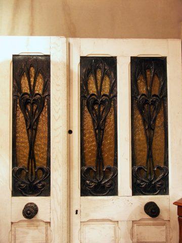 Trois retours de grand balcon n° 2 sur une menuiserie de porte tiercée datant sans doute des années 10 ou 20. Ces panneaux sont présentés à l'envers, comme sur la planche 5 du catalogue Guimard.